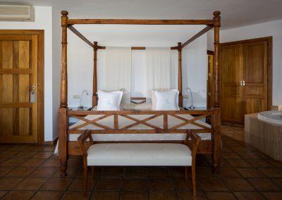 Cama con dosel en habitación con bañera de hidromasaje - Boutique Hotel el Tío Kiko
